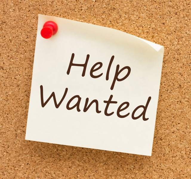 A sticky note on a cork board with the words help wanted on it